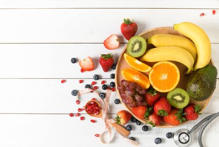 Mixed fresh fruit salad with strawberry with Stethoscope and blank notebook on wooden white background. Diet fruits concept and Flat lay, top view.
