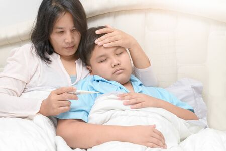 Mother checking temperature of her sick son with high fever, worry and health care concept.