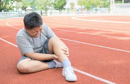 Asian fat boy holding his sports leg injury. muscle painful during training. kid runner having calf ache and problem after running on track. sport and healthy concepts.
