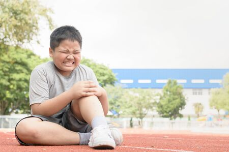Kid athlete suffering form running knee or kneecap injury during outdoor workout on track.