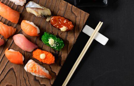 close up of sashimi sushi set with chopsticks and Shoyu sauce on old brown stone background, Japanese food