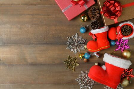 Small santa claus boot with decorations and gift boxes on wooden board, Christmas background and top view