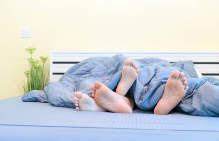 Two pairs of feet of kids. Brother and sister lying under blanket in bed, relax and resting concept.