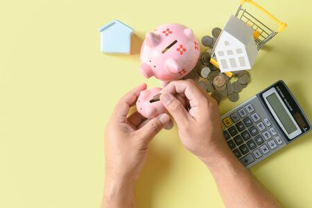Hand putting coin to piggy bank on top view, saving money for buy new house isolated on yellow Stock Photo