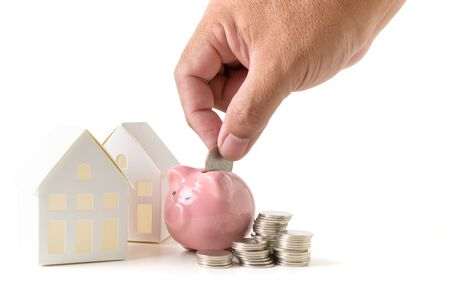 Hand putting coin to piggy bank, saving money for buy new house isolated on white