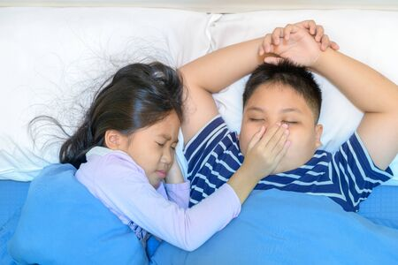 Sister covered her brother's mouth because the snoring is very loud.