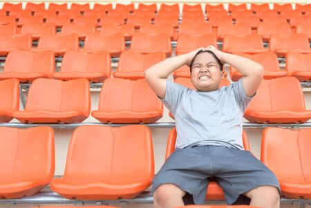 Fat boy is exciting and sit in the football grandstand and waits for the start of the game championship. 版權商用圖片 - 136752648