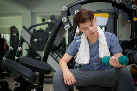 Handsome asian man lifting dumbbells in weight training fitness - Sport and Lifestyle Concept.