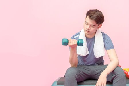 Young handsome fitness man lifting dumbbell on pink
