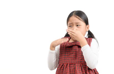 Cute asian girl  squeezing nose with fingers with disgust expression, eager to slip away from bad smell indoors.