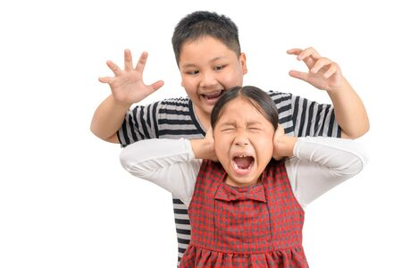 Angry elder brother attcks his sister isolated on white background, playful concept.