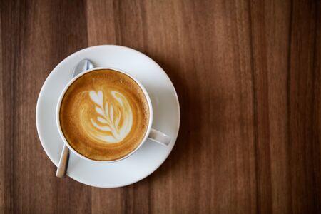 eine Tasse Latte-Art-Kaffee auf Holzhintergrund mit Kopierraum