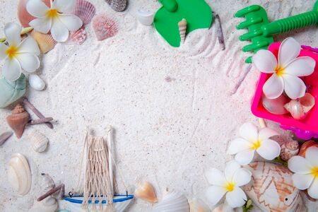 Toys kid with sea shells and plumeria flowers on sand