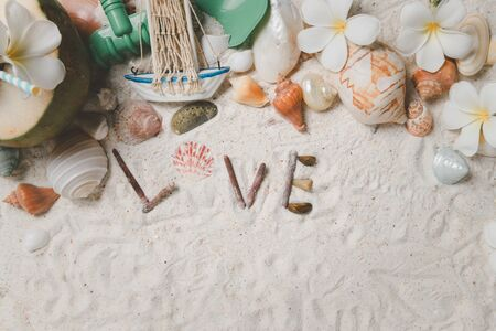 Love text with Shells and plumeria flowers on sand