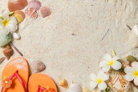 Orange sandal with Shells and plumeria flowers on sand