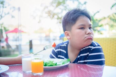 Obese fat boy with expression of disgust against vegetables in salad, Refusing food concept