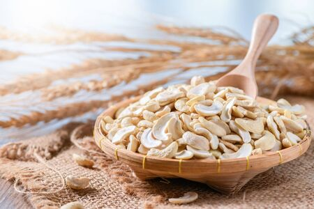 Half raw cashews nuts in bamboo basket on sack, That is beneficial to health Eaten as a snack is tasty and contains vitamins Imagens