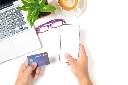 Hand  man using smartphone and credit card for online shopping on white table with latte art hot coffee isolated on white background, top view and copy space for in put text. Shopping online and new normal concept.