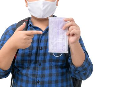 Fat student wears mask and points his finger at a surgical mask isolated on white. Important equipment used to prevent flu and corona virus or covid-19 when going to school. New normal concept