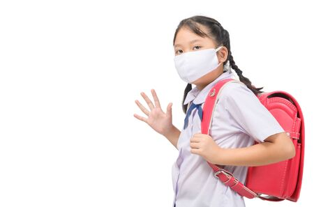 Asian girl student wear mask and waving goodbye before go to school isolated on white background. back to school with new normal concept