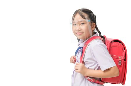 Cute girl student wearing face shield and carries school bag isolated on white background. against and  prevent corona virus covid 19 and new normal education concept Stock Photo