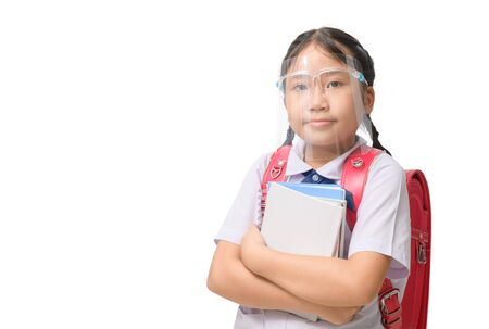 Cute girl student wearing face shield holding book and carries school bag isolated on white background. against and  prevent corona virus covid 19 and new normal education concept Stock Photo