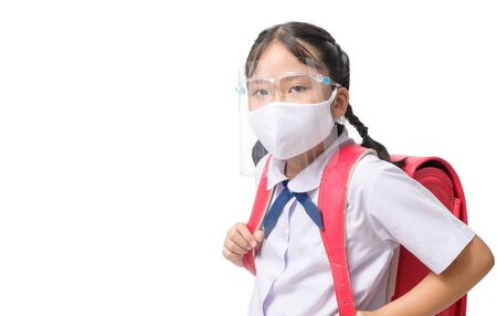 Asian girl student wear face shield and mask  carries school bag isolated on white background. against and  prevent corona virus covid 19 and new normal back to school concept