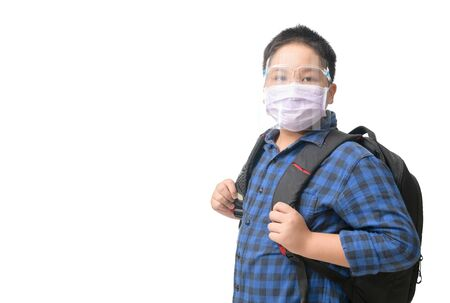 Asian boy student wear face shield and mask  carries school bag isolated on white background. against and  prevent corona virus covid 19 and new normal back to school concept