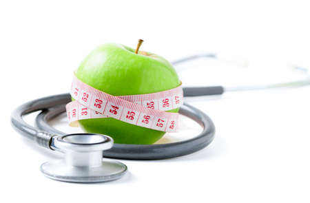 Measuring tape wrapped around a green apple with  stethoscope isolated on white  background, Concept of the goal to lose weight,the goal of diet