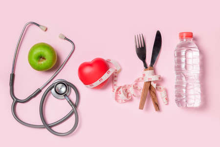 Green apple with stethoscope and measuring tape around fork and knife isolated on pink background, Concept of the goal to lose weight,the goal of diet