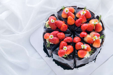 Chocolate cake decorated with fresh strawberry on white cloth, cake and bakery concept