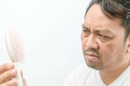 Middle-aged man looking at comb brush with loss hair and stressed about his hair loss problems isolated on white background, Health care concept