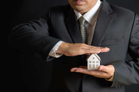 Paper house is covered by business man hands of a real estate agent to protect the house for customers, homebuyers, insurance, ready give to with new owner. Home insurance sales concept.