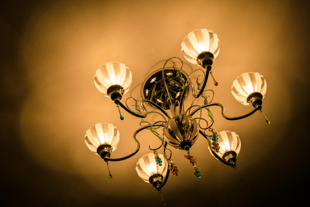 home lighting: Light from the chandelier as if it was some communication with us. Stock Photo