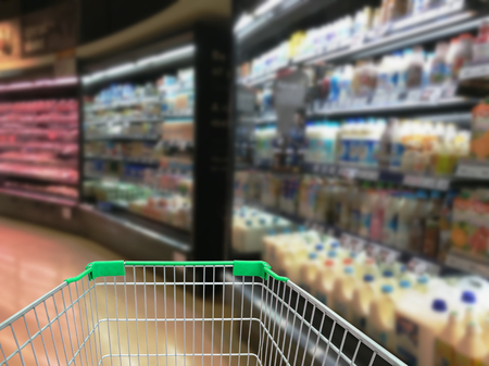 Selection of yogurts, soy milk and milk on the shelves in a supermarket with shopping cart