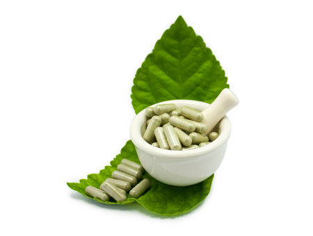 herbal medicine capsule in in the mortar with green leaves an alternative medicine isolated on white background
