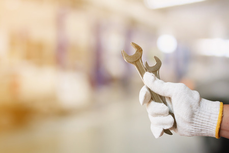 servicing: Mechanic holding pair of wrench at car servicing centre