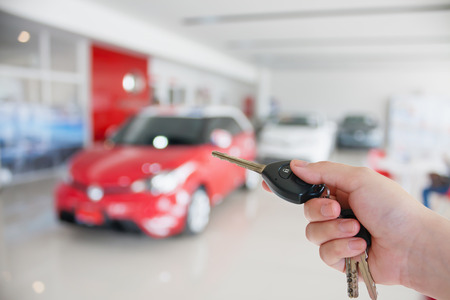 hand holding car keys at new car showroom, buying new car concept
