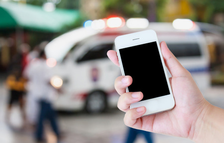 responding: hand hold smartphone with Ambulance responding to an emergency call background