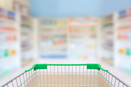 blur shelves of drugs in the pharmacy with shopping cart 版權商用圖片