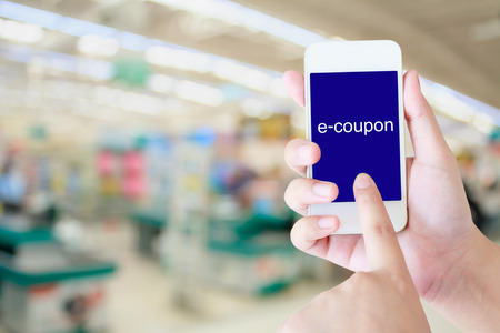 supermarket checkout: Hand holding mobile phone at supermarket checkout background, e coupon concept