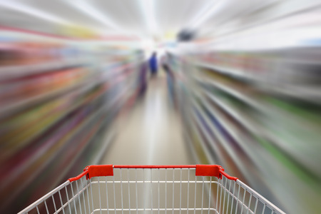 convenience: shopping cart in convenience store shelves blurred background Stock Photo
