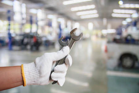 Hand of professional Auto mechanic with wrench, Auto repair service
