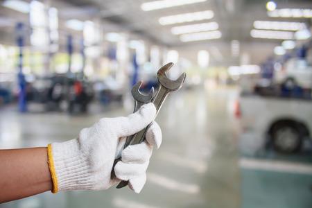 Ręka profesjonalnego mechanika samochodowego z kluczem, serwis samochodowy