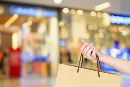 clothing stores: hand hold shopping bag in clothing store