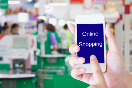 supermarket checkout: Hand holding mobile phone at supermarket checkout background, online shopping concept Stock Photo