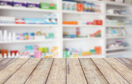 wood counter product display with blur shelves of drugs in the pharmacy