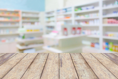 wood counter product display with pharmacy store drugs shelves interior blurred background