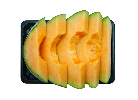 Slices Melon on black plastic plate isolated on the white background