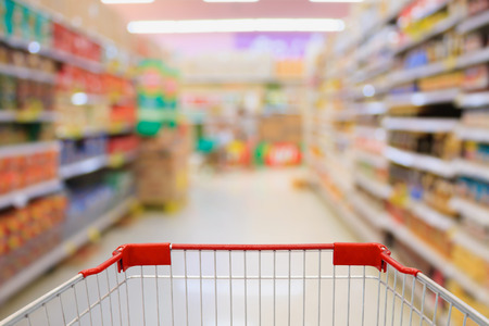Shopping Cart View on Supermarket Aisle interior blurred background 스톡 콘텐츠